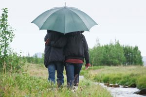 Couple walking together under umbrella by stream