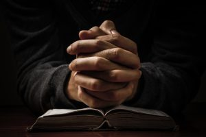 Hands clasped in prayer and resting on book