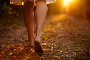 View of a person's legs walking towards the sunset on a dirt road