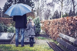 Tall adult in jeans and coat holds hand of child in dress coat with long hair as they stand at a gravestone on a rainy day