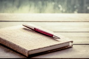 Pen lies on notebook on wooden table with rainy weather visible outside window