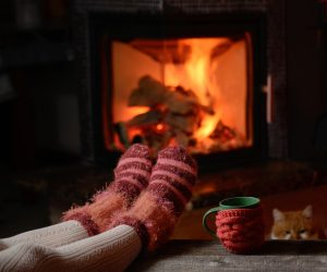 Legs in socks rest in front of fireplace in dark room, with a red and green mug nearby
