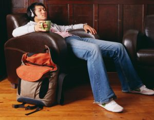 Young adult holds mug of tea and reclines in armchair wearing headphones