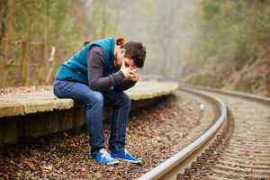 Fall scene of young adult with head in hands sits on ledge next to curving train track