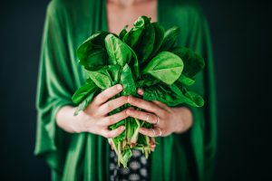 Person in green wrap holds out bunch of spinach in hands
