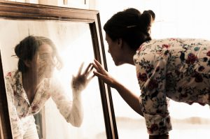 Person leans toward large mirror, fingers to glass. The face is distorted.