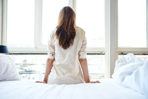 Rear view of adult sitting on bed in pajamas looking out