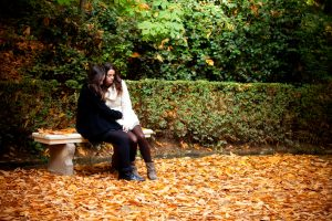 Two young people with long hair wearing coats and warm clothes sit on a bench in carpet of autumn leaves
