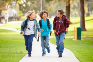 Group of three preteen age kids wearing jeans and backpacks talking happily while walking down path in park