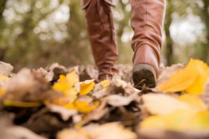 Close-up photo of booted feet walking through leaves