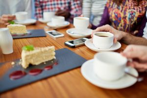 Focus on cake and tea at restaurant table, cropped view of several friends with smartphones on table