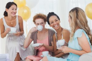 Small group of friends in dresses drink tea and laugh together on sofa at party