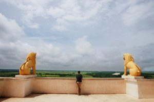Rear view of a man on terrace between two gold statues
