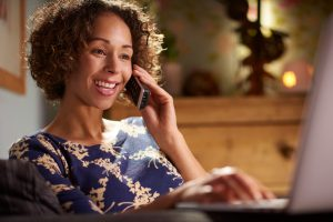 Person with short curly hair talks on cordless phone, smiling, while using laptop