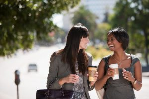 Two women in business attire walk down path holding coffee, talking and laughing