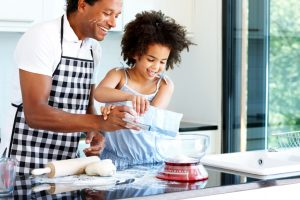 Father and child of 6-8 years wear aprons and prepare a meal in the kitchen together smiling