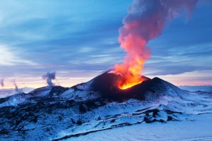 Volcano on snowy mountain beginning to erupt