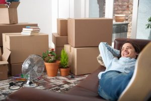 Person wearing jeans and button-down shirt lies on sofa, looking content, with open and packed boxes all over room