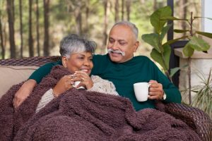 Senior couple sit on porch and talk, holding mugs, covered by a fuzzy blanket