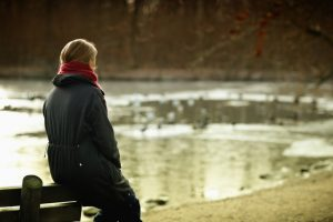 Person wearing red scarf and black coat sits on back of bench and looks out at lake