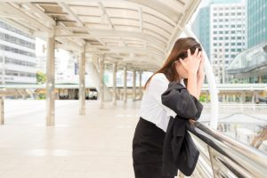 Stressed woman leaning against railing