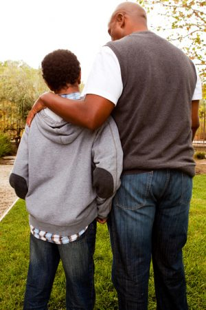 Rear view of father with arm on shoulders of teenager