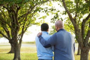 Rear view photo of father and son in trees having a talk