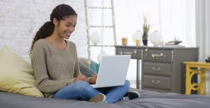 Teenager smiles while sitting on bed in decorated bedroom, legs crossed, using laptop