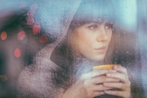 Person with long hair and bangs wearing hood holds mug close to face and looks out window on rainy day