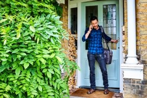 young adult in plaid shirt and jeans with leather bag speaks on phone while leaving house