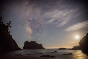 Milky Way and moon at dawn over California beach