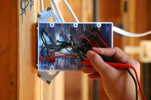 Hand using tool works to test wires in circuit switch box