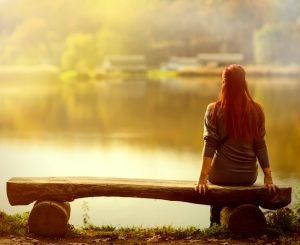 Rear view of person with long red hair sitting on bench at sunset looking over lake