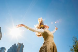 Person in gold dress with long hair stretches arms out, spinning under blue sky