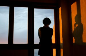 Person in shadow looking out high window into cloudy sky