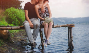 Teen couple sitting by the lake