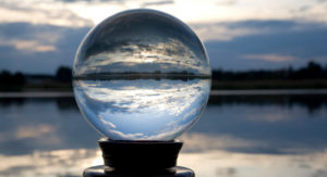Crystal ball on stand by sea reflects cloud and sea view