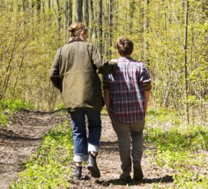 A photograph showing the rear view of mother and her teenage son going for a walk in the country