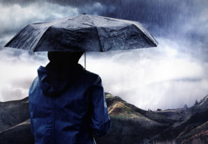 Person under umbrella looking at scenery in rain