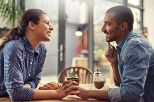 Shot of a young couple enjoying their date at a local coffee shop talking holding hands