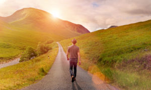 Rear view of person in casual clothes and hat walking alone on a narrow country road through a green valley surrounded by mountains, heading toward the rising sun. Warm sunlight with lens flare. Taking decisions and choosing a direction for new beginnings, following the way forward, not looking back.