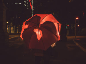 Silhouettes of couple about to kiss are visible behind a red umbrella