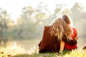 Rear view of two young adults with long hair sitting on grass. one hugs the other