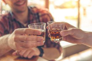 Cropped image of two people clinking shot glasses together for toast