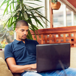 Person with shaved head wearing polo shirt sits in bright cafe and uses laptop computer with serious expression