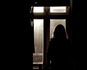 Silhouette of person looking out window