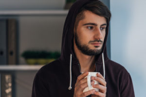 Portrait of pensive young adult in hooded shirt holding coffee cup and looking away while standing at home