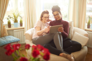 Couple sits together with legs crossed together using tablet and smiling