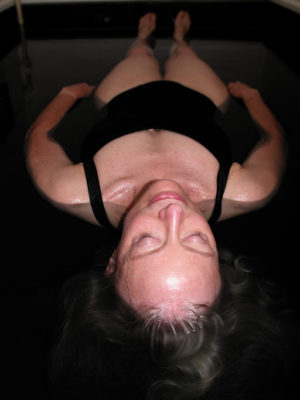 Photo shows a person with long hair wearing black tank-style swimsuit floating in sensory deprivation tank with eyes closed