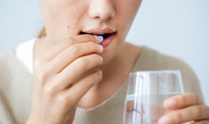 Close-up image of lower face of person taking a blue pill while holding a glass of water